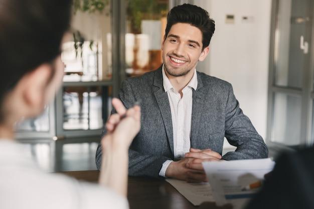 Geschäfts-, karriere- und vermittlungskonzept - lächelnder kaukasischer mann der 30er jahre, der mit dem ausschuss der geschäftsmäßigen leute während des vorstellungsgesprächs im amt verhandelt