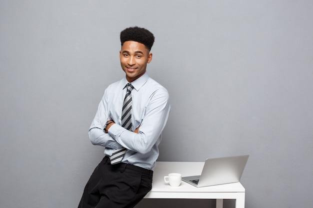 Geschäfts-konzept - porträt des afroamerikanergeschäftsmannes, der den kaffee sitzt an einem schreibtisch unter verwendung eines laptops spricht und trinkt.