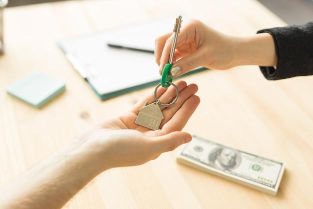 Geschäfts-, makler- und immobilienkonzept - hand-zu-hand-schlüssel von neuem zuhause.