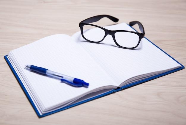 Geschäfts- oder bildungskonzept - notizbuch, stift und brille auf dem tisch