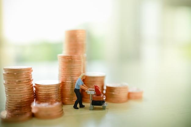 Geschäfts-, reise-, geld- und sparkonzept. schließen sie oben von reisenden miniaturfigur menschen mit flughafenwagen und koffer mit stapel kupfermünzen auf holztisch.