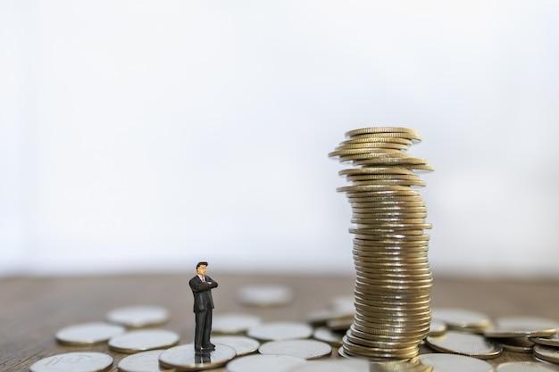 Geschäfts-, risiko-, investitions- und sparkonzept. schließen sie oben von geschäftsmann-miniaturmenschen, die stehen und zu instabilem stapel von münzen mit kopienraum suchen.