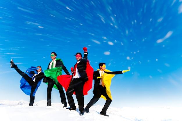 Geschäfts-superhelden, die im schneesturm aufwerfen