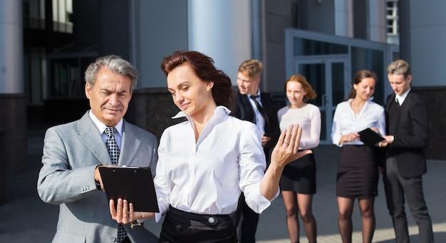 Geschäfts-, technologie- und bürokonzept - lächelndes geschäftsteam mit laptop-computern und dokumenten, die diskussion haben