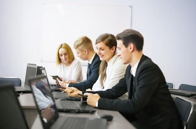Geschäfts-, technologie- und bürokonzept - lächelndes geschäftsteam mit laptops und dokumenten, die diskussion im büro haben