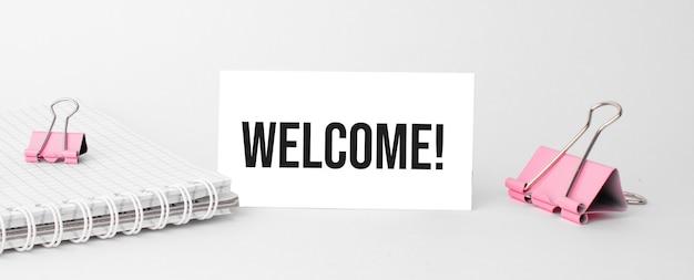 Geschäfts- und finanzkonzept. auf dem tisch liegt ein notizbuch, ein stift und eine visitenkarte mit der aufschrift - willkommen