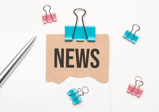 Geschäfts- und finanzkonzept. auf weißem hintergrund liegt ein notizbuch, ein stift, wäscheklammern und pappe mit der aufschrift - news