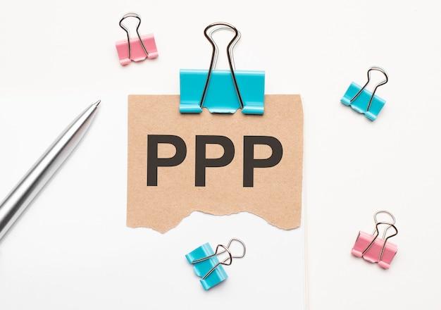 Geschäfts- und finanzkonzept. auf weißem hintergrund liegt ein notizbuch, ein stift, wäscheklammern und pappe mit der aufschrift - ppp
