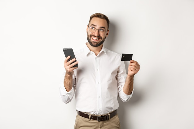 Geschäfts- und online-zahlung. bild des gutaussehenden mannes denkend, während kreditkarte und smartphone, die gegen weißen hintergrund stehen.