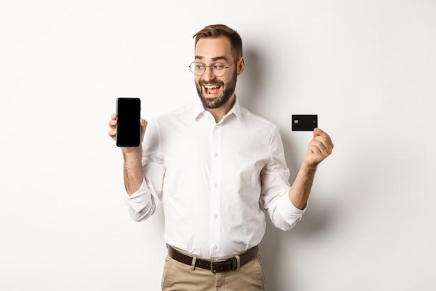 Geschäfts- und online-zahlung. lächelnder hübscher mann, der mobilen bildschirm und kreditkarte zeigt, über weißem hintergrund stehend.