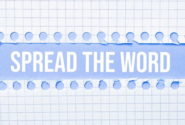 Geschäfts- und rechtskonzept. zwischen zwei notizbüchern auf blauem hintergrund die aufschrift - spread the word
