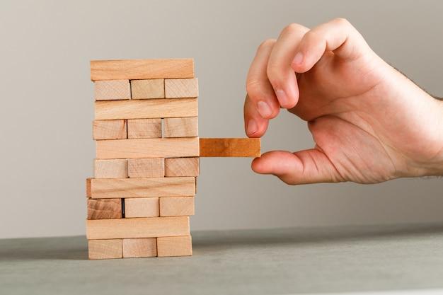 Geschäfts- und risiko- und managementkonzept auf grauer und weißer wandseitenansicht. hand holt holzblock heraus.
