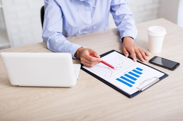Geschäfts- und statistikkonzept geschäftsfrau im modernen büro mit blick auf diagramme und grafiken