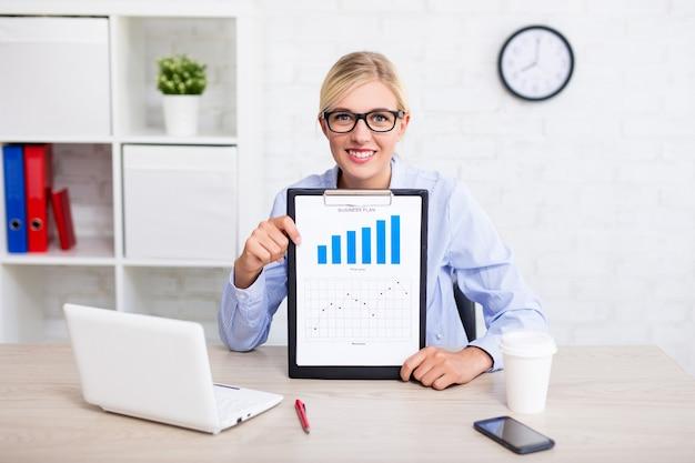 Geschäfts- und statistikkonzeptfrau im büro, die zwischenablage mit diagrammen und diagrammen zeigt