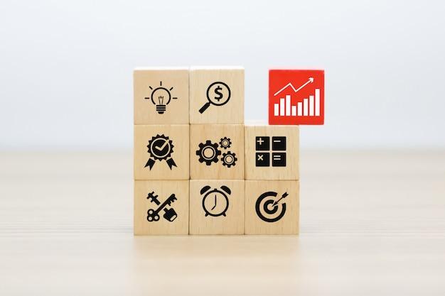Geschäfts- und wachstumsgraphiken ikonen auf holzklötzen.