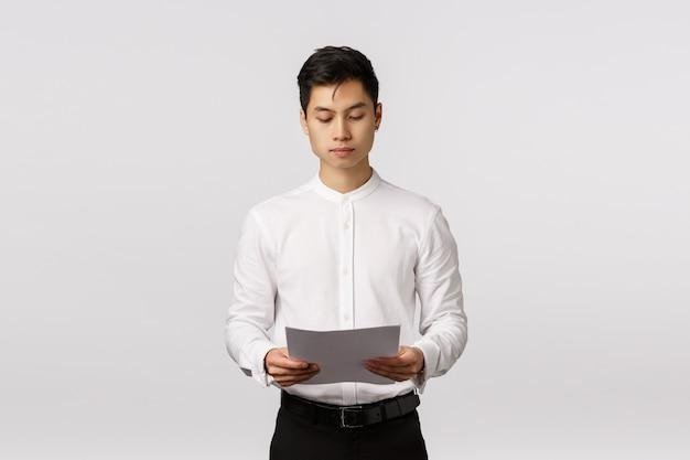 Geschäfts-, unternehmensökonomie- und leutekonzept. der ernst schauende beschäftigte elegante asiatische männliche unternehmer, der dokumente verwahrt, papier lesend, bereiten sich für bürositzung vor und studieren finanzbericht