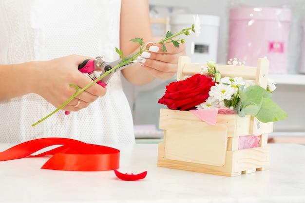 Geschäfts-, verkaufs- und blumenkonzept - nahaufnahme der floristenfrau, die bündel am blumenladen hält. weiche schattierungen frischer frühlingsblumen.