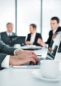 Geschäftsambiente, arbeitend an laptop während des treffens