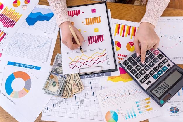 Geschäftsanalyse mit dollar-banknoten, grafiken und taschenrechner
