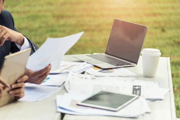 Geschäftsanalysedokument mit tablette und laptop auf tabelle im garten.