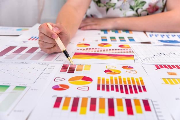 Geschäftsanalyst, der auf diagramm mit kugelschreiber zeigt