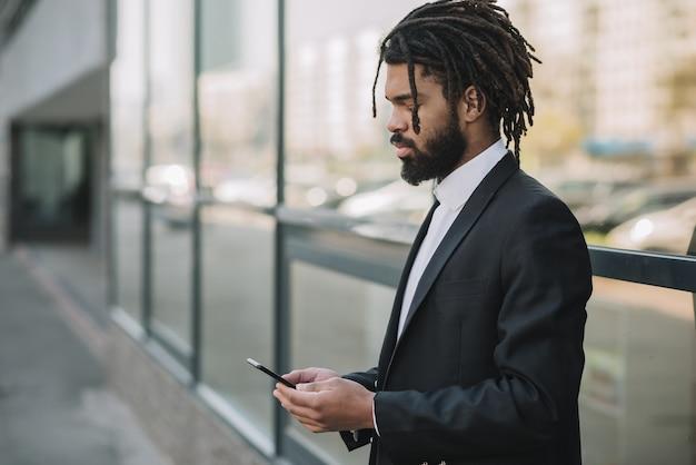 Geschäftsangestellter, der telefonseitenansicht hält