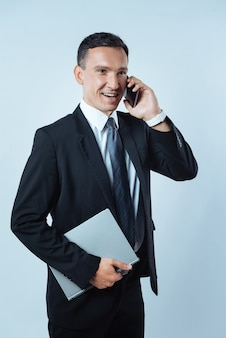 Geschäftsanruf. erfreut über einen fröhlichen, netten mann, der sein handy in der hand hält und während der arbeit einen anruf tätigt