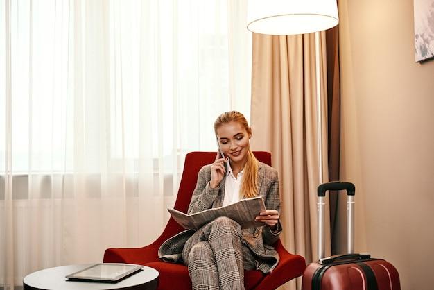 Geschäftsanruf im hotelzimmer auf geschäftsreise. junge und stilvolle geschäftsfrau mit koffer und smartphone, die auf dem sofa im hotelzimmer sitzt. digitales tablet am tisch