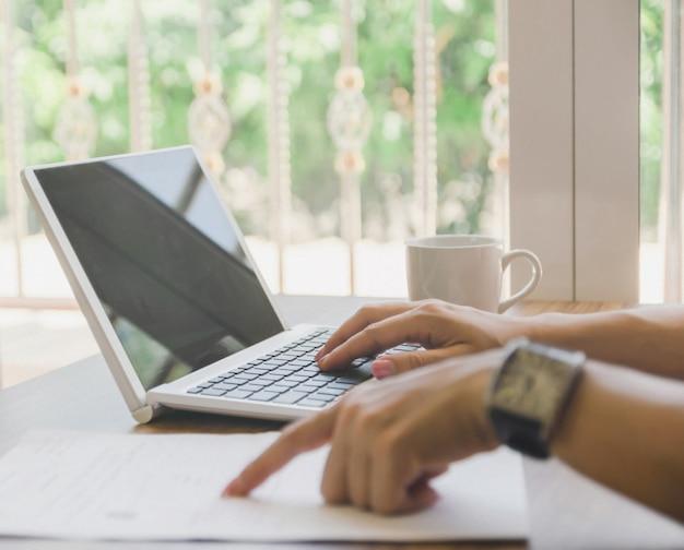 Geschäftsarbeit und computertechnologie das schreibtischnotizbuch auf hölzerner tabellenideendarstellung.