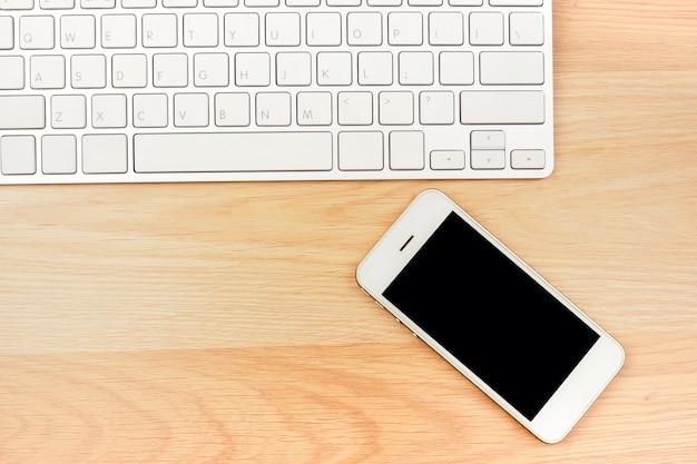Geschäftsarbeits-smartphone-laptop auf braunem holztisch. draufsicht