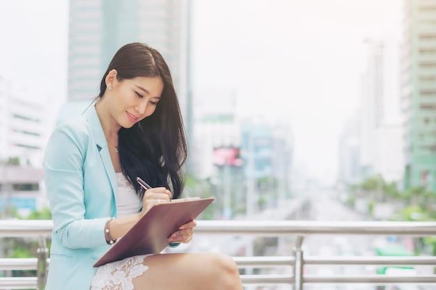 Geschäftsasiatische angestellte setzt sich hin und schreibt die papiere auf, die sie für die arbeit außerhalb des büros vorbereitet hat. sie arbeitet mit einem lächeln und ist glücklich - lifestyle-geschäftsleute-konzept