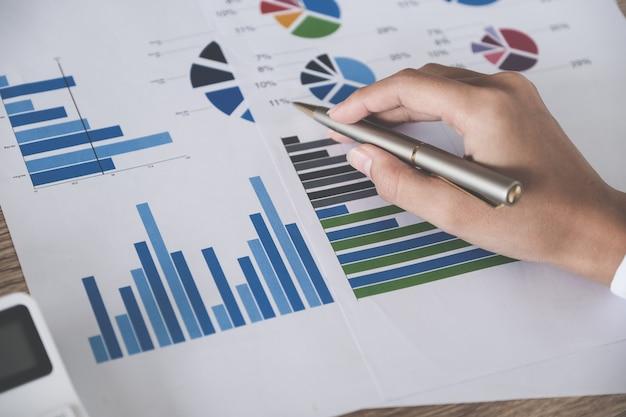 Geschäftsbuchhaltungskonzept, geschäftsmannstift, der diagramm zeigt und taschenrechner zur berechnung des budgets und des darlehenspapiers im büro verwendet.