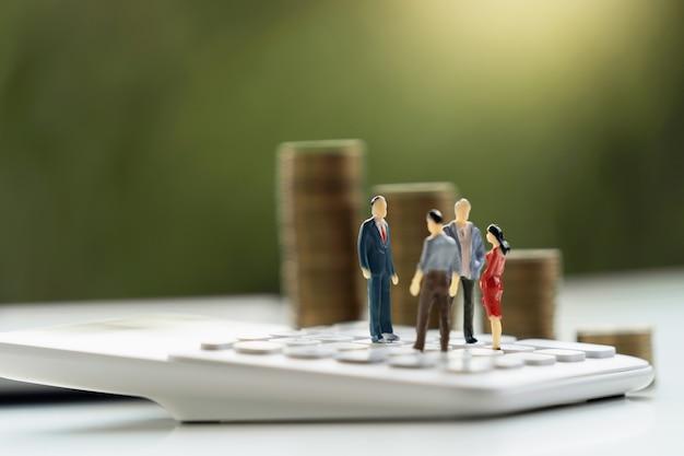 Geschäftsbuchhaltungskonzept. miniaturspielzeugtreffen auf taschenrechner mit geldstapel