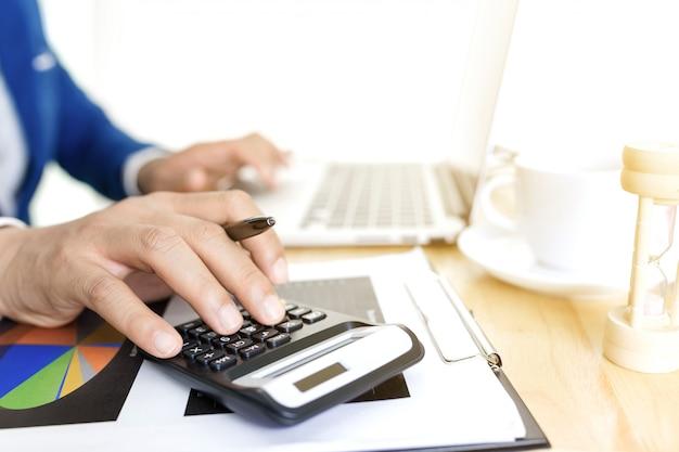 Geschäftsbuchhaltungsplankonzept, arbeitend an tischplattenlaptop-computer mit taschenrechner für die herstellung des geschäfts, geschäftsmannhand, die mit laptop-computer auf hölzernem schreibtischgeschäftsinvestitionsberater arbeitet.