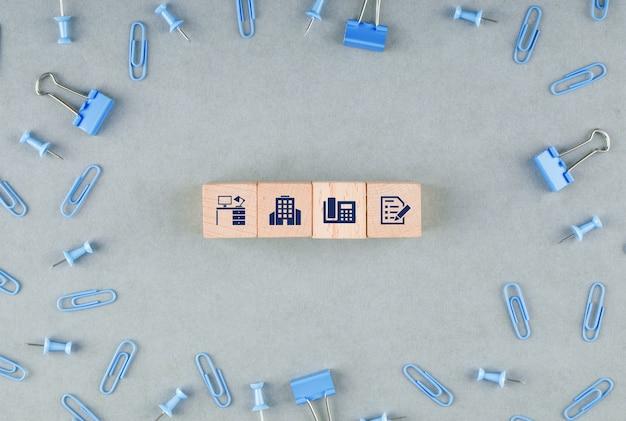 Geschäftsbürokonzept mit holzklötzen mit ikonen, büroklammern, binderclips draufsicht.