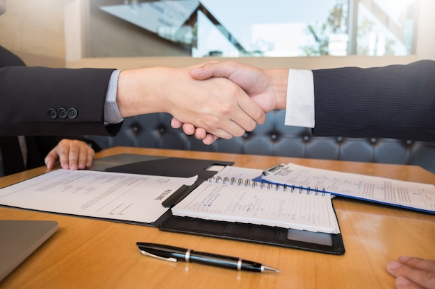 Geschäftschef und angestelltenhändeschütteln nach erfolgreichen verhandlungen oder interview.