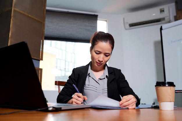 Geschäftsdame, die dokumente unterschreibt
