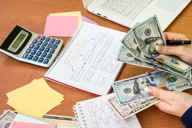 Geschäftsdame, die dollarbanknoten für die realisierung des geschäftsplans zählt