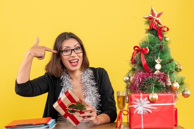 Geschäftsdame im anzug mit brille, die ihr geschenk hält und an einem tisch mit einem weihnachtsbaum darauf im büro sitzt