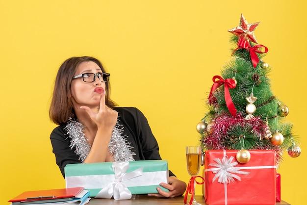 Geschäftsdame im anzug mit brille, die ihr geschenk überraschend hält und an einem tisch mit einem weihnachtsbaum darauf im büro sitzt