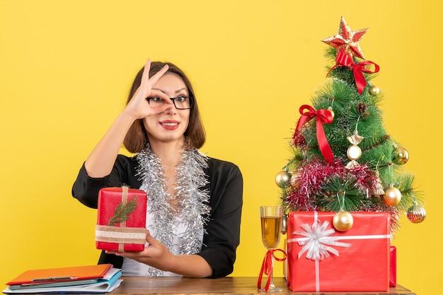 Geschäftsdame im anzug mit brille, die ihr geschenk zeigt, das brillengesten macht und an einem tisch mit einem weihnachtsbaum darauf im büro sitzt