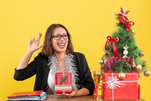 Geschäftsdame im anzug mit brille, die ihr geschenk zeigt, das etwas konzentriert und an einem tisch mit einem weihnachtsbaum darauf im büro sitzt