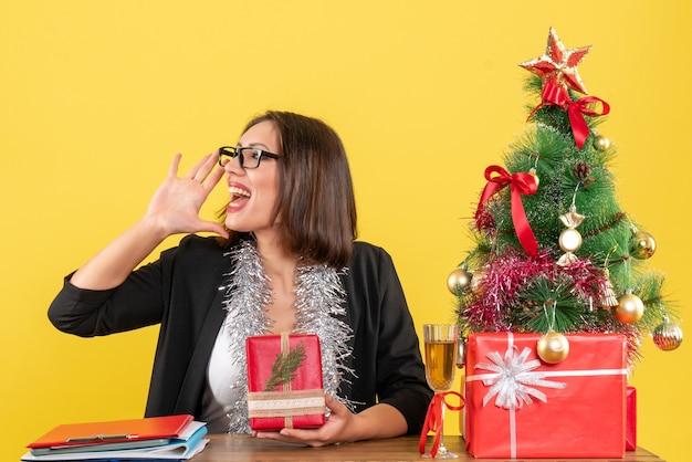 Geschäftsdame im anzug mit brille, die ihr geschenk zeigt, das jemanden anruft und an einem tisch mit einem weihnachtsbaum darauf im büro sitzt