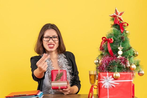 Geschäftsdame im anzug mit brille, die ihr geschenk zeigt, etwas fragend und an einem tisch mit einem weihnachtsbaum darauf im büro sitzend