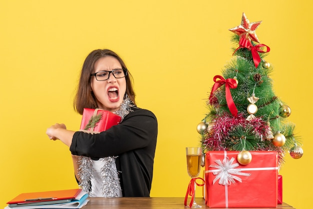 Geschäftsdame im anzug mit brille versteckt ihr geschenk nervös und sitzt an einem tisch mit einem weihnachtsbaum darauf im büro