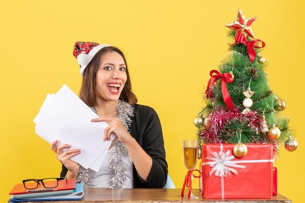 Geschäftsdame im anzug mit weihnachtsmannhut und neujahrsdekorationen, die allein arbeiten und an einem tisch mit einem weihnachtsbaum darauf im büro sitzen