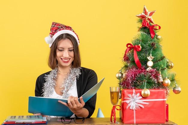Geschäftsdame im anzug mit weihnachtsmannhut und neujahrsdekorationen, die dokument lesen und an einem tisch mit einem weihnachtsbaum darauf im büro sitzen