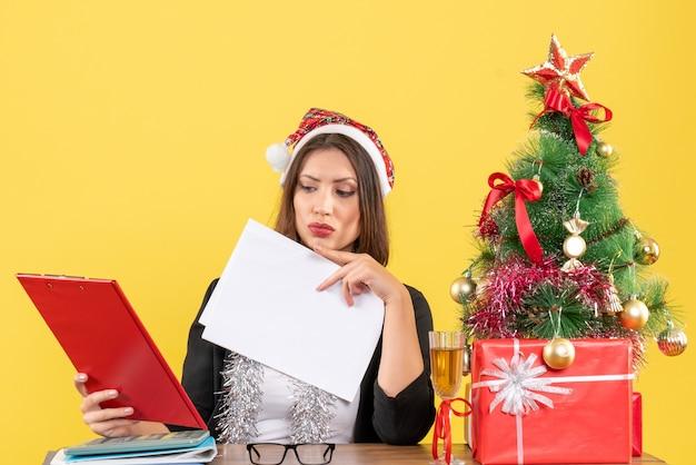 Geschäftsdame im anzug mit weihnachtsmannhut und neujahrsdekorationen, die dokument prüfen und an einem tisch mit einem weihnachtsbaum darauf im büro sitzen