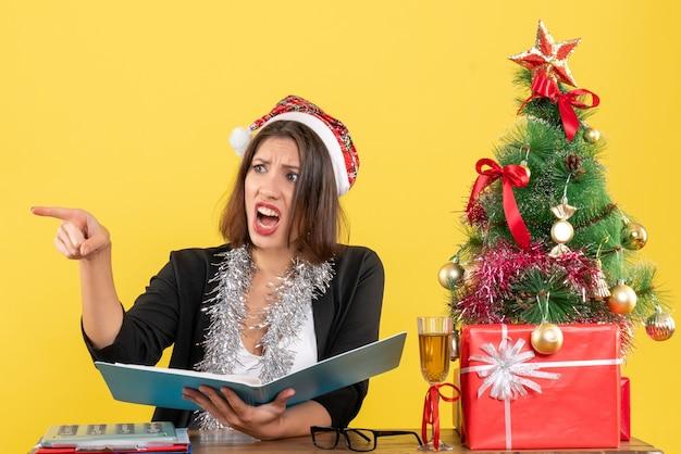 Geschäftsdame im anzug mit weihnachtsmannhut und neujahrsdekorationen, die dokument überprüfen, das etwas zeigt und an einem tisch mit einem weihnachtsbaum darauf im büro sitzt