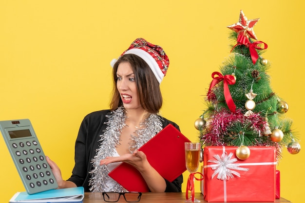 Geschäftsdame im anzug mit weihnachtsmannhut und neujahrsdekorationen, die taschenrechner zeigen und an einem tisch mit einem weihnachtsbaum darauf im büro sitzen